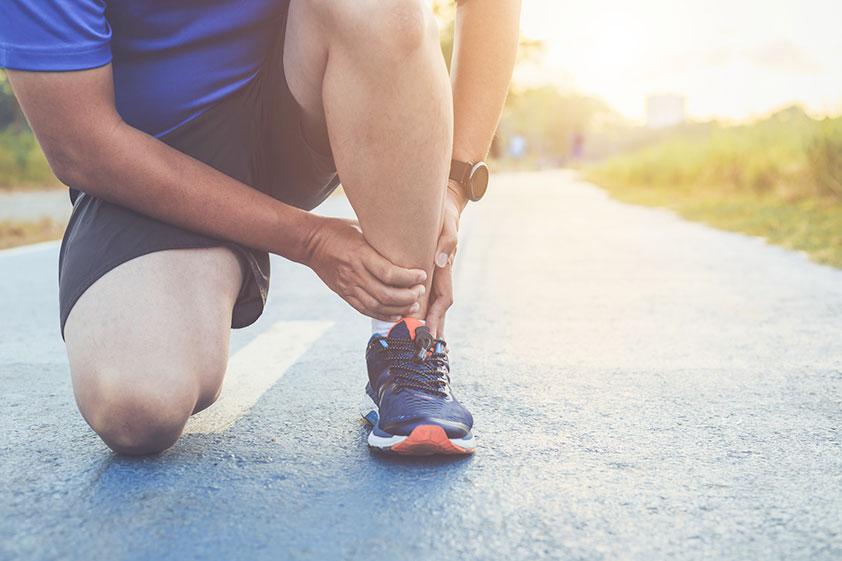 Kniender Läufer der sein schmerzendes Sprunggelenk anfasst.