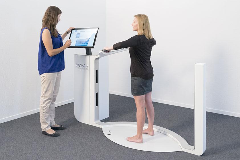 Medizinprodukte Beraterin misst in der Kabine anhand des digitalen 3D-Beinscanners die Beine der Kundin aus, um sie mit passenden Kompressionstrümpfen zu versorgen.