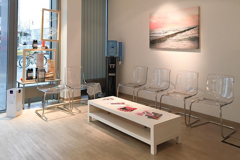 Blick auf den Wartebereich der Filiale alphamed ausgestattet mit Acryl-Stühlen, Zeitschriften, Beistelltisch und einem Wasserspender.