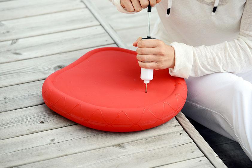 Teilansicht einer Frau, die hockend, in weißer Freizeitbekleidung, mithilfe einer Luftpumpe mit Nadelventil ein luftbefüllbares Sitzkissen aufpumpt.