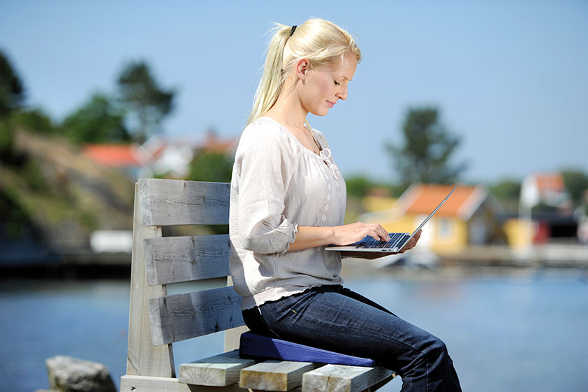 Seitlicher Blick auf eine blonde Frau mit Pferdeschwanz sitzend auf einem Keilkissen auf einer Holzbank am Bootssteg.