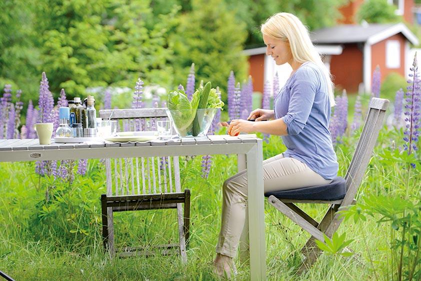 Seitlicher Blick auf eine blonde Frau mit Pferdeschwanz sitzend am Holztisch im sommerlich grünen Garten zwischen violett blühenden Lupinen.