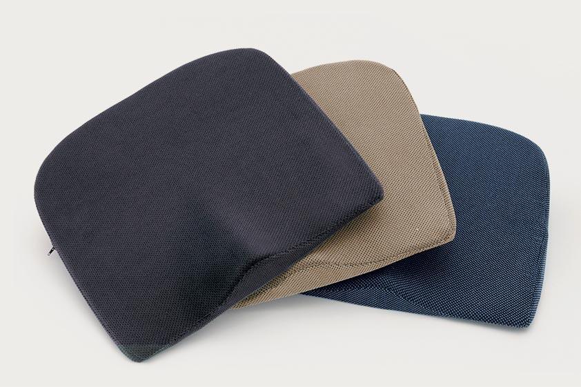 Im Halbkreis aufgereihte Keilkissen mit abnehmbarem  und waschbarem Veloursbezug in drei verschiedenen Farben: schwarz, beige und dunkelblau.