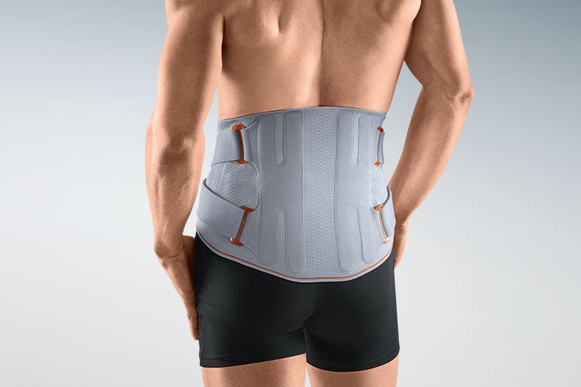 Männertorso, freistehend mit dem Rücken zum Betrachter gewandt und nacktem Oberkörper, trägt über seine schwarzen Boxer-Unterhose eine graue Lumbal-Stützorthese zur Entlastung der Lendenwirbelsäule.