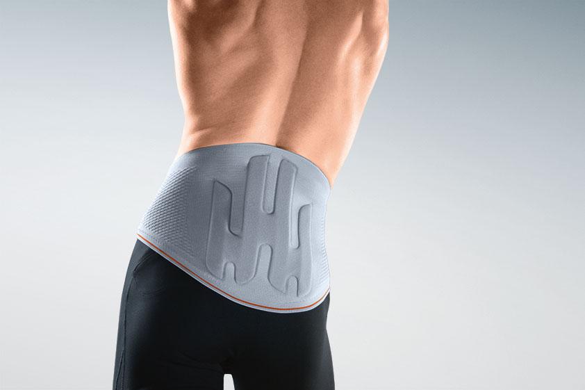 Männertorso, freistehend mit dem Rücken zum Betrachter gewandt und nacktem Oberkörper, trägt eine  Rückenbandage über seiner schwarzen Boxer-Unterhose.