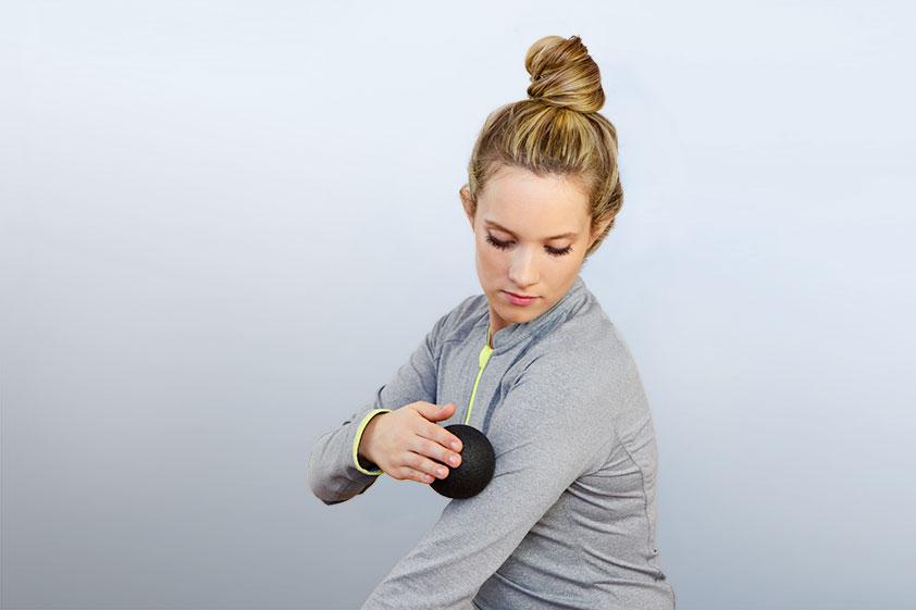 Zusehen ist eine junge Frau mit halbgedrehten Oberkörper zum Betrachter. Sie trägt eine graue Sportjacke mit neongelbem Reißverschluß. Ihre blonden Haare sind zu einem Knoten hochgesteckt und ihr Kopf und ihr Blick sind leicht nach unten zur linken Schulter geneigt. Der rechte Arm ist nach oben angewinkelt, um mit der rechten Hand mit Hilfe einer kleinen, schwarzen Faszienkugel den linken Arm zu massieren.